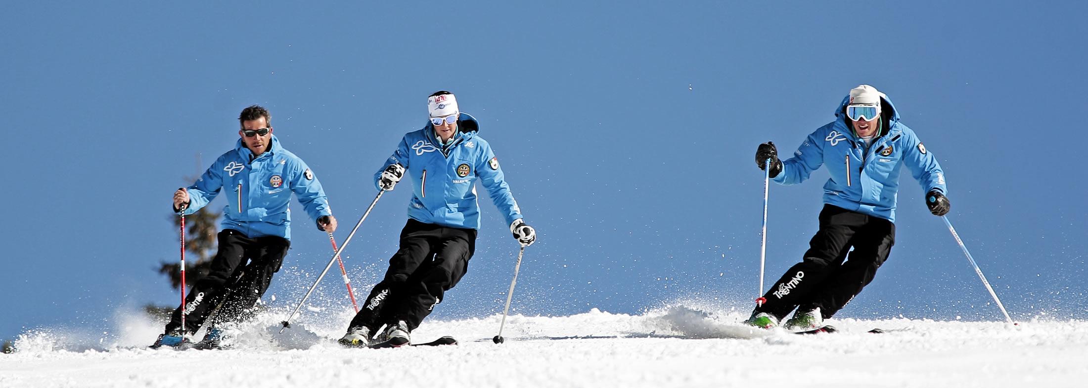 Gruppo di sciatori che scendono la montagna innevata con gli sci