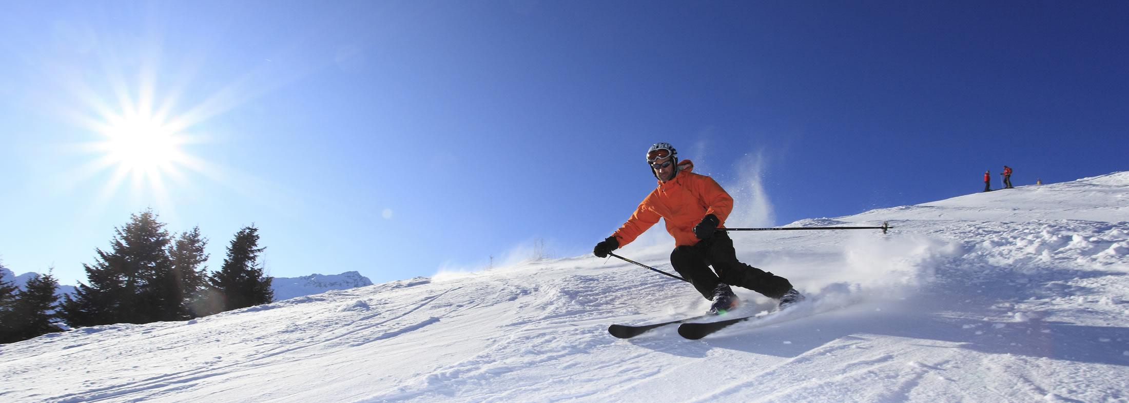 ragazzo con tuta arancione scende una montagna innevata sugli sci